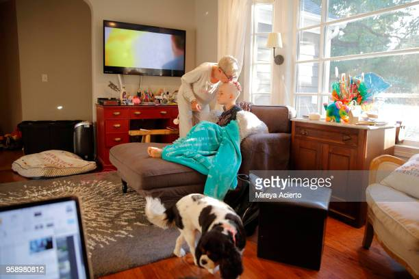 An older woman kisses the top of a young girl with cancer, while she sits in front of the television, in the living room.