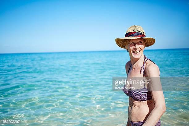 an older woman laughing on sunny day at the beach - eine seniorin allein stock-fotos und bilder