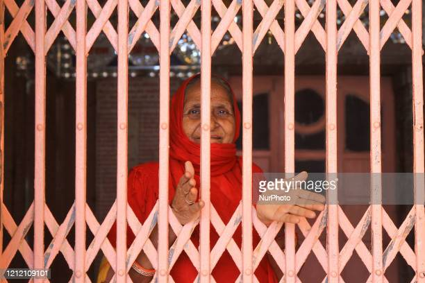 An older woman look out during the nation wide lockdown imposed in the wake of deadly novel coronavirus pandemic in JaipurRajasthan IndiaMay 072020