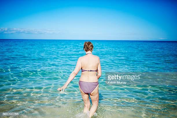 an older woman paddles in the sea by the beach - eine seniorin allein stock-fotos und bilder