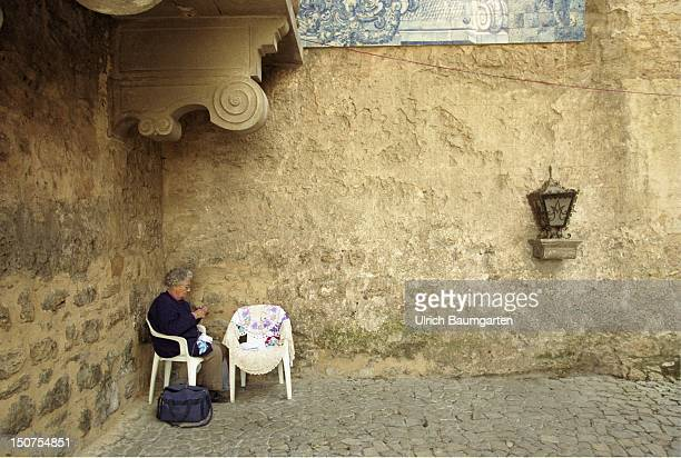 An older woman stis knitly in a corner of the defence wall in Obidos, a small medieval town in Portugal.