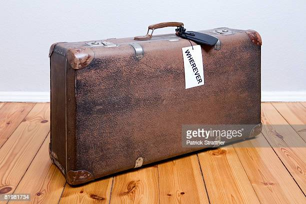 An old-fashioned suitcase with a ?wherever? luggage tag