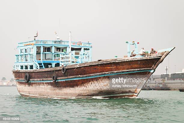 An old-style wooden cargo boat travels along Dubai Creek in the United Arab Emirates.