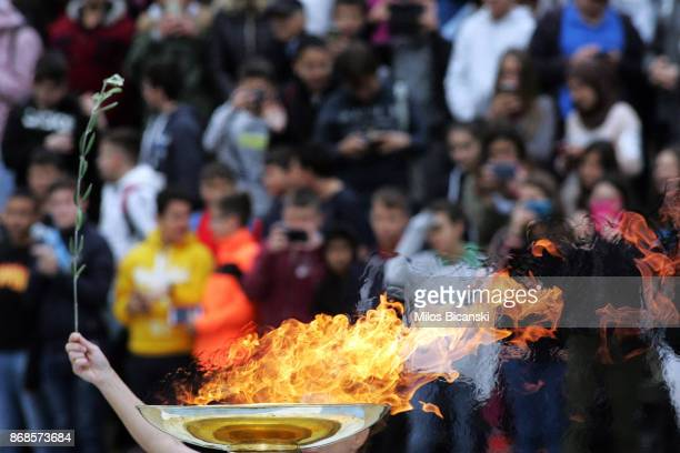 An olive tree branch is held up near the Olympic flame at The Panathenaic Stadium during the handover ceremony of the Olympic flame for the 2018...