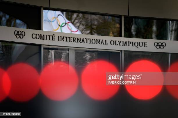 An Olympic flag is seen in window's reflection at the entrance of the headquarters of the International Olympic Committee in Lausanne on March 24,...