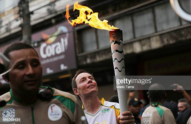 An Olympic torchbearer carries the flame ahead of the Rio 2016 Olympic Games on August 2 2016 in Sao Goncalo Rio de Janeiro state Brazil The torch...