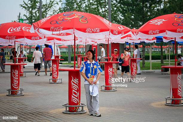 An Olympic volunteer stands near the Coca-Cola Co. Sponsored food and beverage area in the Olympic Green facility at the 2008 Beijing Olympics in...