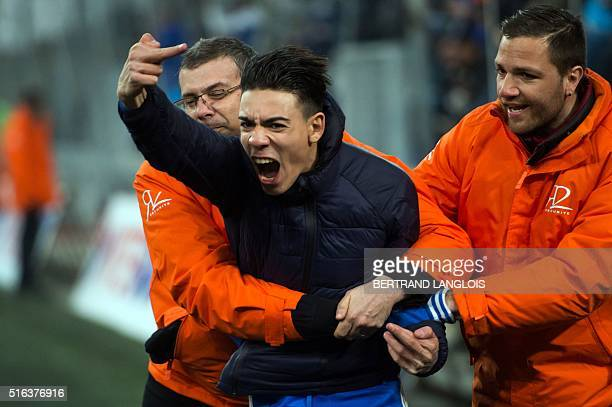An OM fan gestures as he is stopped by security officers during the French L1 football match Olympique de Marseille vs Rennes on March 18 2016 at the...
