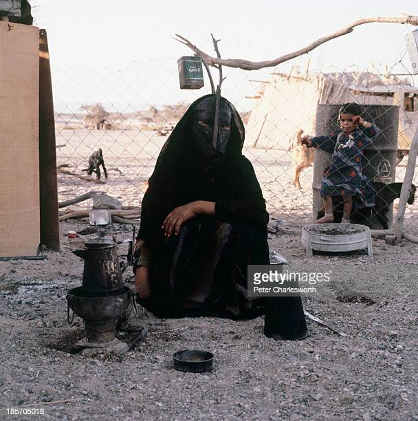 An Omani bedhouin woman making tea over an open fire wearing a black burka with a traditional face mask is watched by a little girl through a fence...