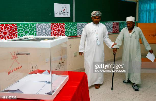 An Omani election official helps an elderly man to cast his ballot for a consultative council at a polling station in Muscat on October 25 where the...
