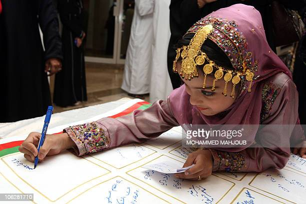 An Omani girl writes a note to Sultan Qaboos on what local women aim to be the longest message of greetings in the world, as part of celebrations...