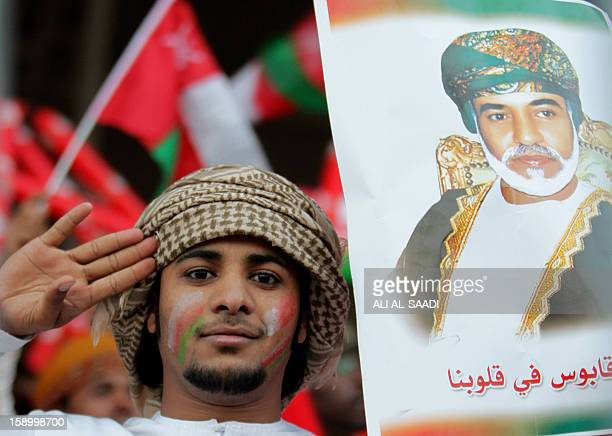 An Omani supporter holds a picture of Omani Sultan Qaboos bin Said prior the sart of the opening ceremony and football match between Bahrain and Oman...