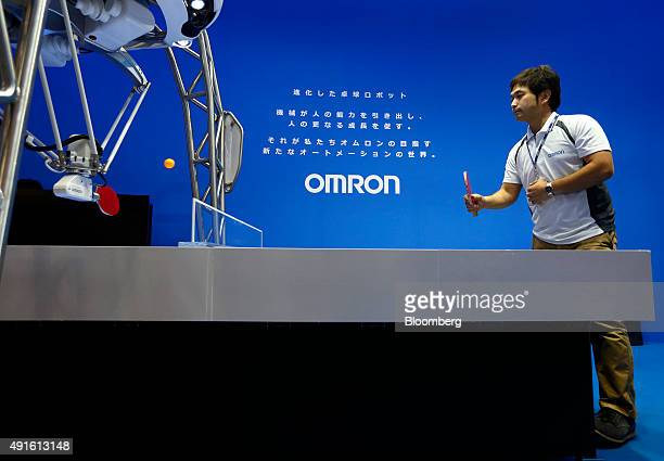 An Omron Corp robotic arm mounted with a table tennis racket demonstrates hitting a ball at the CuttingEdge IT Electronics Comprehensive Exhibition...