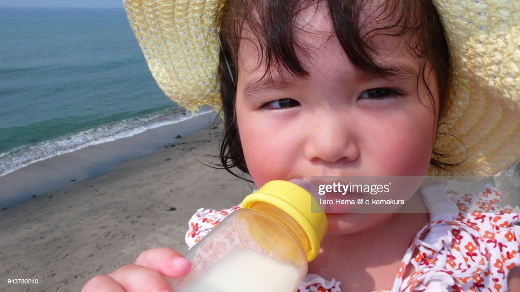 An one-year-old girl drinking milk on the beach : ストックフォト