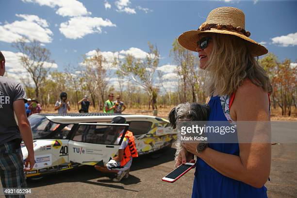 An onlooker holding a small dog watches on as Stella Lux of Solar Team Eindhoven Netherlands in the Cruiser Class stops at the first control point...