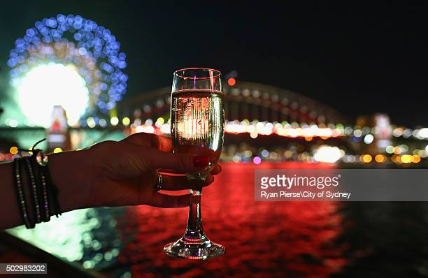 An onlooker holds a glass of champagne as the 9pm Fireworks explode off the Sydney Harbour Bridge on New Year's Eve on Sydney Harbour on December 31...