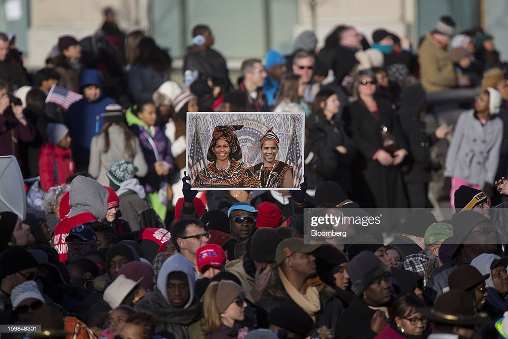 An onlooker holds a photograph of U.S. President Barack Obama and first lady Michelle Obama while standing along the parade route during the presidential inauguration in Washington, D.C., U.S., on Monday, Jan. 21, 2013. A crowd estimated by police to be as large as 700,000, including warmly dressed women with American flags stuck in their hair, a smattering of celebrities and many Republicans, gathered today to witness Obama take his second oath of office on the steps of the U.S. Capitol. Photographer: Victor J. Blue/Bloomberg via Getty Images