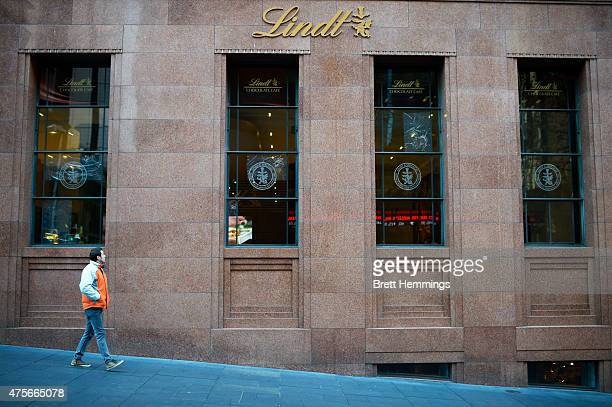 An onlooker inspects a smashed window at the Lindt Cafe at Martin Place on June 3 2015 in Sydney Australia Sydney's Lindt Cafe had its windows broken...