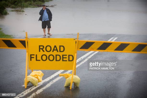 An onlooker looks at floodwaters washing over a closed road in Brisbane on March 30 2017 Torrential rain hampered relief efforts after powerful...