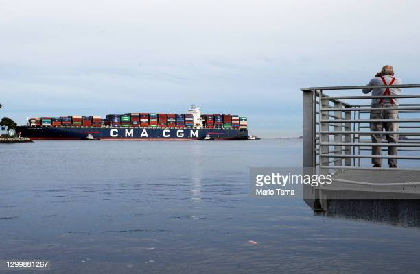 An onlooker takes photos as a container ship enters the Port of Los Angeles on February 1, 2021 in San Pedro, California. As of January 28, a record...