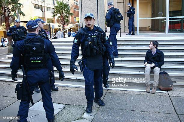 An onlooker watches as police cordon off the area he was sitting during 'Reclaim Australia' in Martin Place on July 19 2015 in Sydney Australia...