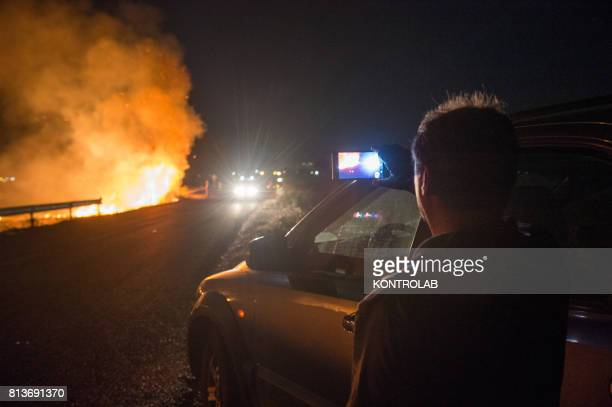 An onlooker watching one of the fires that struck Cosentino in Calabria and blazed throughout the day and night destroying thousands of hectares of...