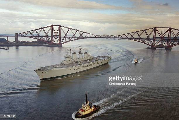An onlooker waves a flag as the Royal Navy aircraft carrier HMS Ark Royal makes her way under the Forth Rail Bridge February 13 2004 outside...