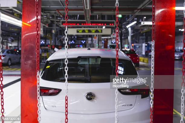 An Opel logo sits on the trunk of a white Opel Astra seen at the Opel automobile plant in Gliwice Poland on Monday March 6 2017 The maker of Peugeot...
