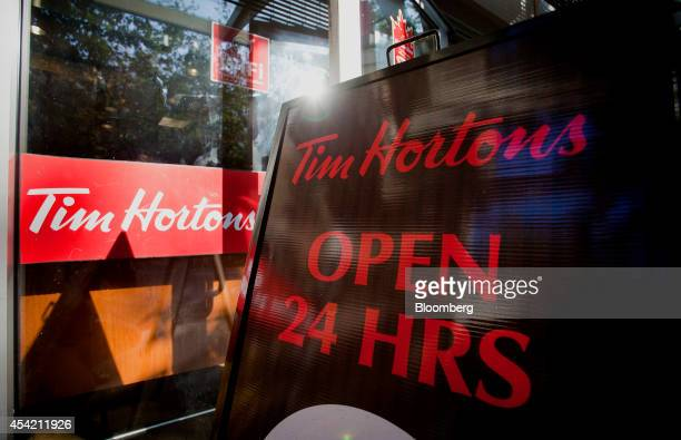 An 'Open 24 Hours' sign is displayed outside of a Tim Hortons Inc restaurant in downtown Vancouver British Columbia Canada on Tuesday Aug 26 2014...