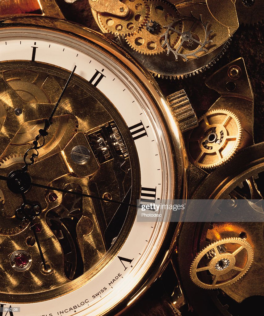 an open antique pocket watch exposes its gears as it sits beside other gears and circles : Foto de stock