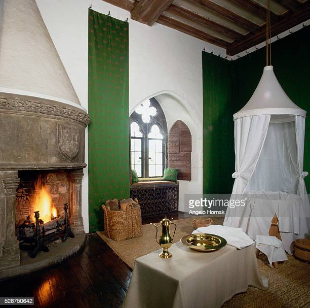 An open fire blazes in the corner of the Queen's Bathroom at Leeds Castle, furnished with a draped tub and wall hangings.