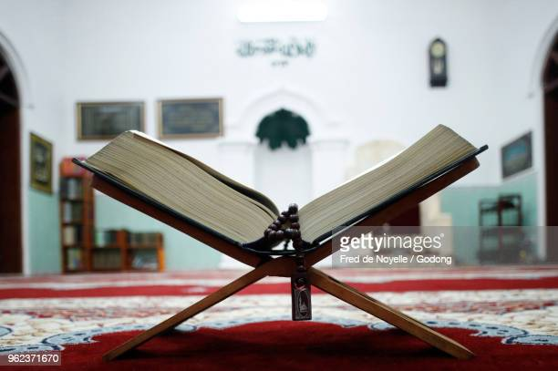 an open holy quran and muslim prayer beads on wood stand with mihrab in background. - holy quran stock pictures, royalty-free photos & images