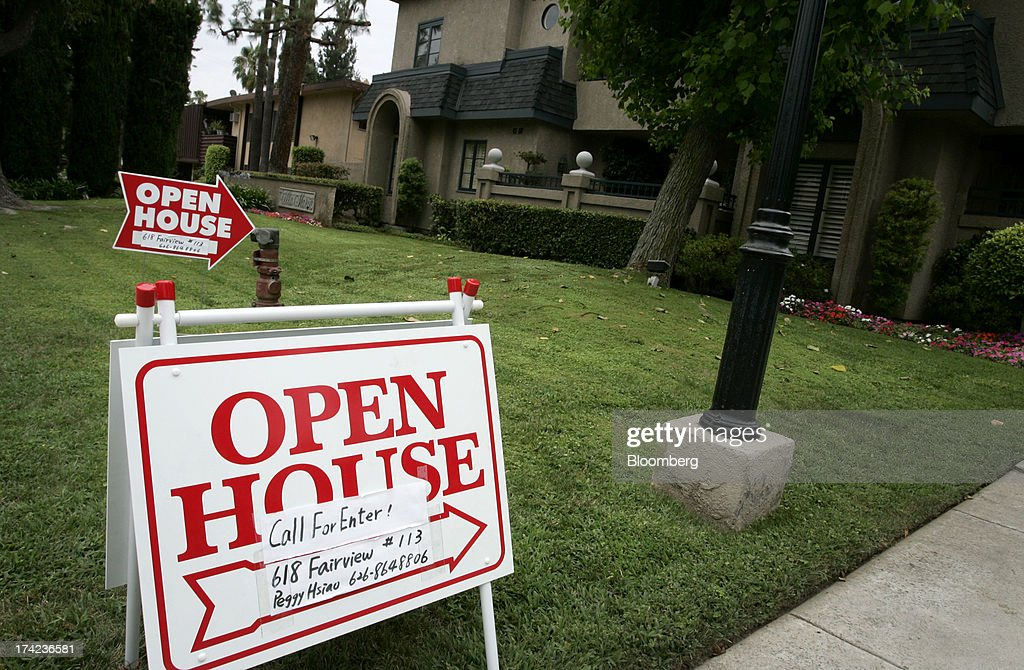 An 'open house' sign stands outside a townhouse complex in Arcadia, California, U.S., on Sunday, July 21, 2013. Sales of previously owned houses unexpectedly dropped in June, hurt by a lack of supply and rising mortgage rates that may slow the rebound in the U.S. real-estate market. Photographer: Jonathan Alcorn/Bloomberg via Getty Images