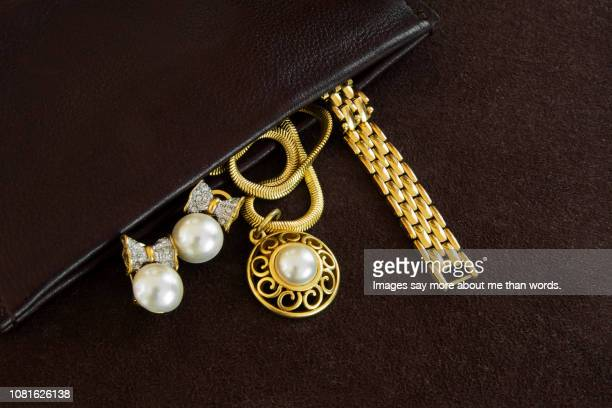 an open leather bag showing some golden jewlery. still life. close eup. - jewelry stock pictures, royalty-free photos & images