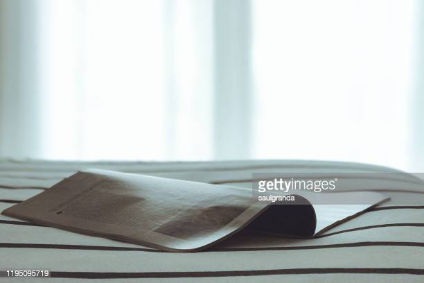 an open magazine on a bed - magazine stock pictures, royalty-free photos & images