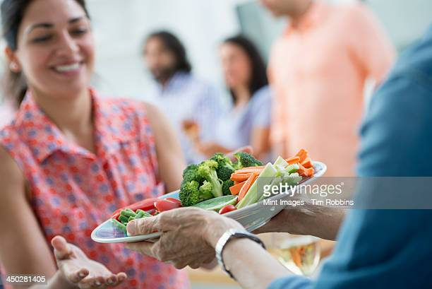 An open plan office in New York City. A working lunch, a salad buffet. A group of men and women of mixed ages and ethnicities meeting together.