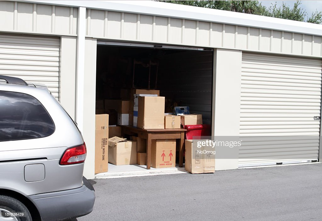 An open self storage unit with a van parked next to it : Stock Photo