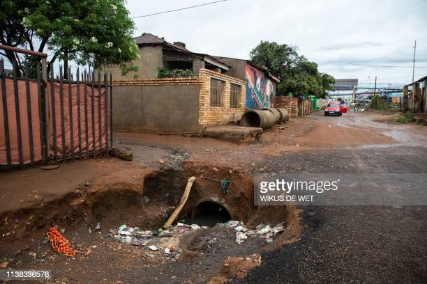 An open storm water drain is visible in the street on April 5 2019 in Kliptown near Soweto South Africa goes to the polls next month the country's...