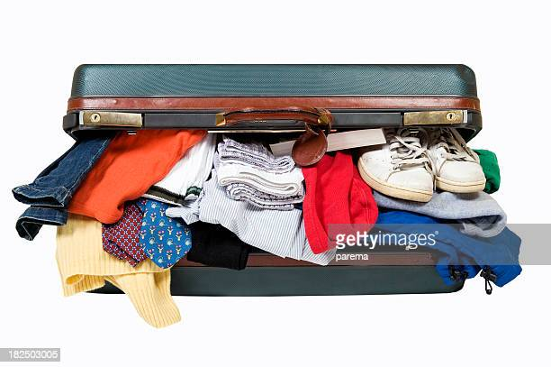 An open suitcase with clothes and shoes falling out of it
