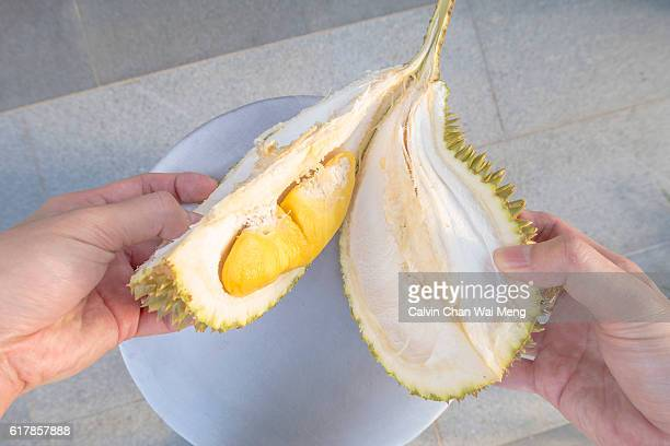 An opened Musang King grade durian with its yellow fruit