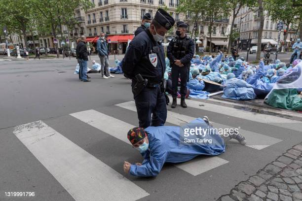 """An operating room nurses crawls across a road during a strike to protest the """"contempt"""" shown to them in a overhaul of France's healthcare system,..."""