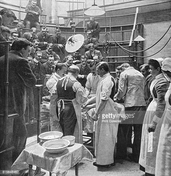 An operation at Charing Cross Hospital London 1901 A team of surgeons work on a patient in the operating theatre of Charing Cross Hospital while men...