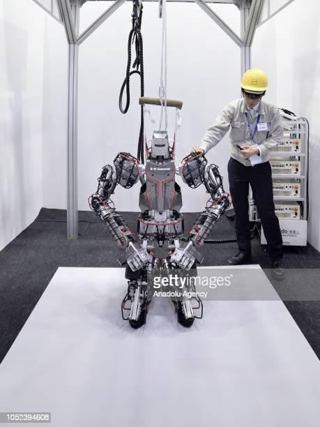 An operator of Kawasaki Heavy Industries Ltd's checks a Kawasaki Heavy Industries Ltd's Kaleido humanoid robot displayed at the Japan Robot Week 2018...