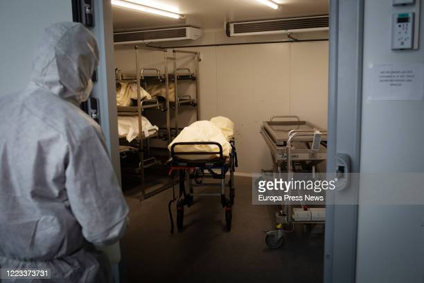 An operator of the Crematorium of Girona, totally protected, moves a coffin of a victim with Covid-19 to a cold room to disinfect it before putting...