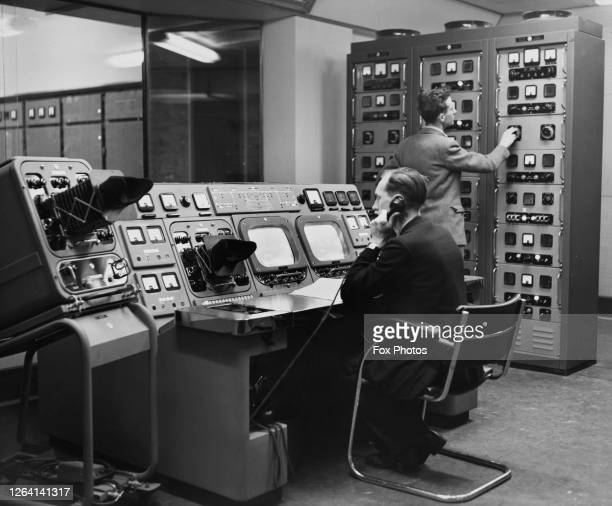 An operator sits at a control desk, while another person adjusts a console to his right, inside the BBC London transmitter at Crystal Palace in south...