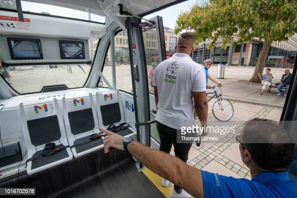 An operator stands in the door of an electric autonomous bus while a passenger waits on August 14 2018 in Mainz Germany Called EMMA the bus is made...