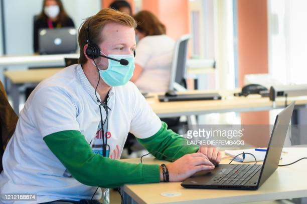 An operator wearing a protective face mask works in a call centre for 'contact tracing' where phonecalls are made to map how many people in Brussels...