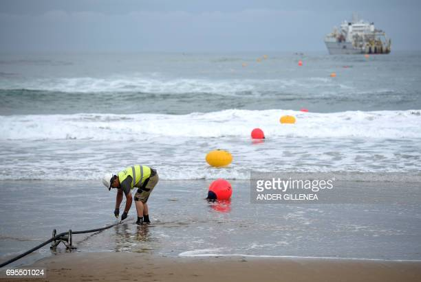 An operator works during the mooring of an undersea fiber optic cable at Arrietara beach near the Spanish Basque village of Sopelana on June 13 2017...