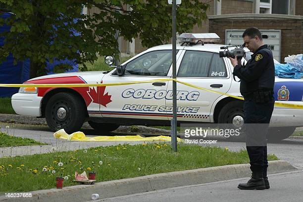 An OPP Forensic officer videos the scene where a Cobourg police officer identified as Constable Chris Garrett died after answering a call to the site...