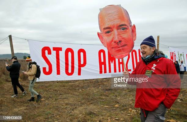 """An opponent holds a cutout sign depicting Amazon CEO Jeff Bezos, in front of a banner reading """"Stop Amazon"""" during a rally against plans to build a..."""